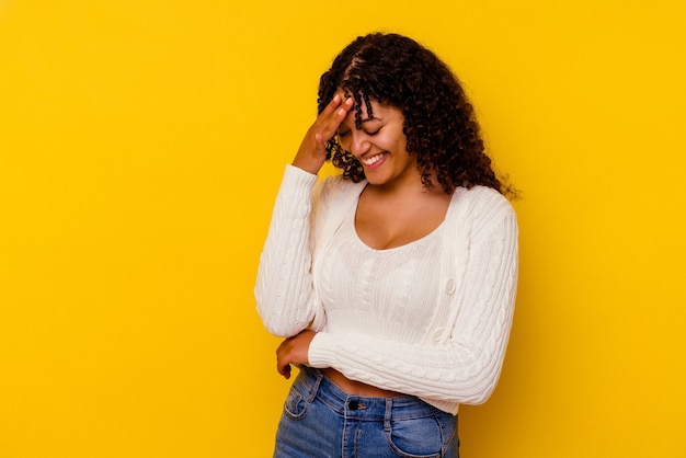 Jonge gemengd ras vrouw geïsoleerd op gele muur knipperen door vingers, beschaamd bedekkend gezicht.
