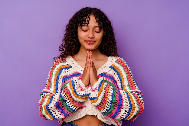 Jonge gemengd ras vrouw geïsoleerd op paarse achtergrond hand in hand bidden in de buurt van mond, voelt zich zelfverzekerd.