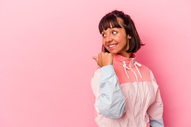 Jonge gemengd ras vrouw geïsoleerd op roze achtergrond punten met duim vinger weg, lachen en zorgeloos.