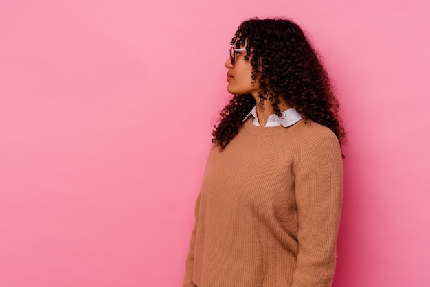 Jonge gemengd ras vrouw geïsoleerd op roze staren naar links, zijwaarts poseren.