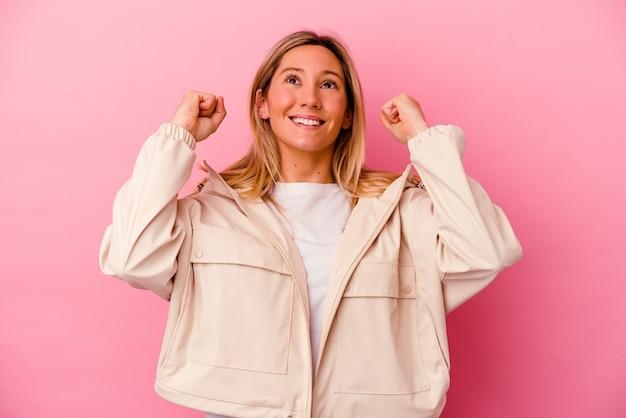 Jonge gemengd ras vrouw geïsoleerd op roze vieren een overwinning, passie en enthousiasme, gelukkige uitdrukking.