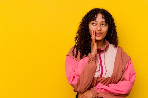 Jonge gemengd ras vrouw geïsoleerd op roze zegt een geheim heet remnieuws en kijkt opzij