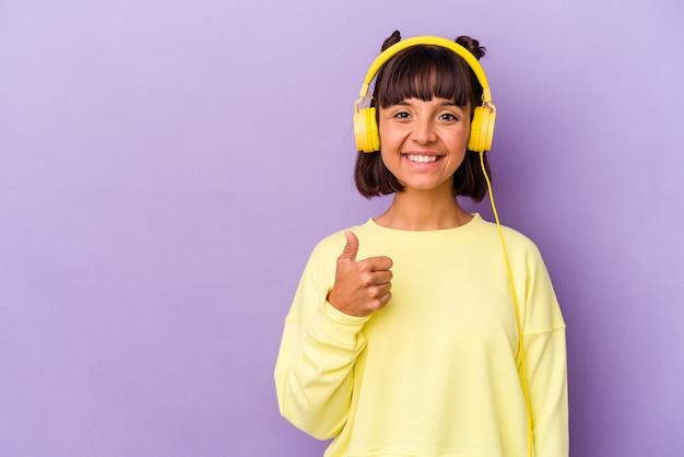 Jonge gemengd ras vrouw luisteren naar muziek geïsoleerd op paarse achtergrond glimlachend en duim omhoog