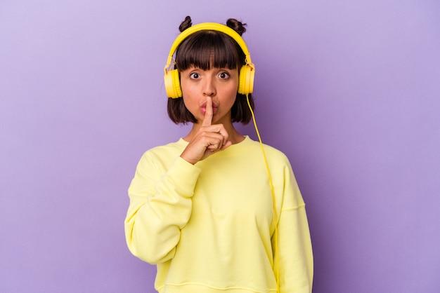 Jonge gemengd ras vrouw luisteren naar muziek geïsoleerd op paarse achtergrond houden een geheim of vragen om stilte.
