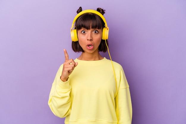 Jonge gemengd ras vrouw luisteren naar muziek geïsoleerd op paarse achtergrond met een idee, inspiratie concept.