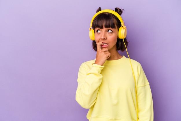 Jonge gemengd ras vrouw luisteren naar muziek geïsoleerd op paarse achtergrond ontspannen denken over iets kijken naar een kopie ruimte.