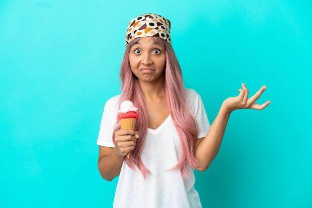 Jonge gemengd ras vrouw met een cornet ijs geïsoleerd op blauwe achtergrond twijfels hebben terwijl het verhogen van handen