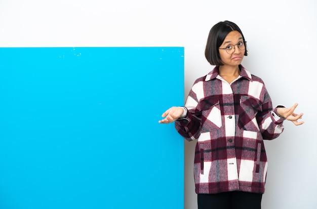 Jonge gemengd ras vrouw met een groot blauw bordje geïsoleerd met twijfels