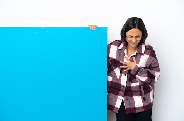 Jonge gemengd ras vrouw met een groot blauw bordje geïsoleerd op een witte achtergrond met pijn in het hart