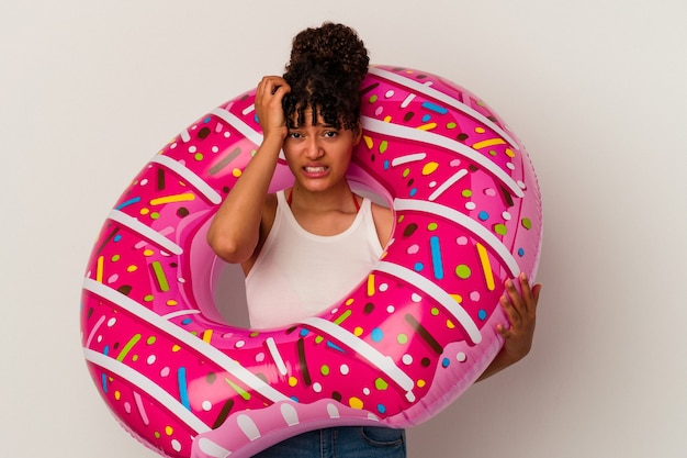 Jonge gemengd ras vrouw met een opblaasbare lucht donut geïsoleerd op een witte achtergrond geschokt, ze heeft een belangrijke vergadering onthouden.