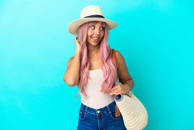 Jonge gemengd ras vrouw met een strandtas met pamela geïsoleerd op blauwe achtergrond denken een idee