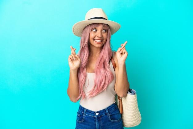 Jonge gemengd ras vrouw met een strandtas met pamela geïsoleerd op blauwe achtergrond met vingers over elkaar