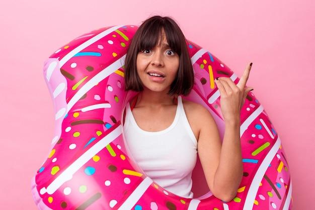 Jonge gemengd ras vrouw met opblaasbare donut geïsoleerd op roze achtergrond met een gebaar van teleurstelling met wijsvinger.