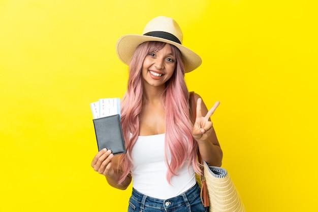 Jonge gemengd ras vrouw met paspoort en strandtas geïsoleerd op gele achtergrond glimlachend en overwinning teken tonen
