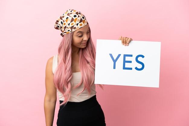 Jonge gemengd ras vrouw met roze haar geïsoleerd op roze achtergrond met een bordje met de tekst yes