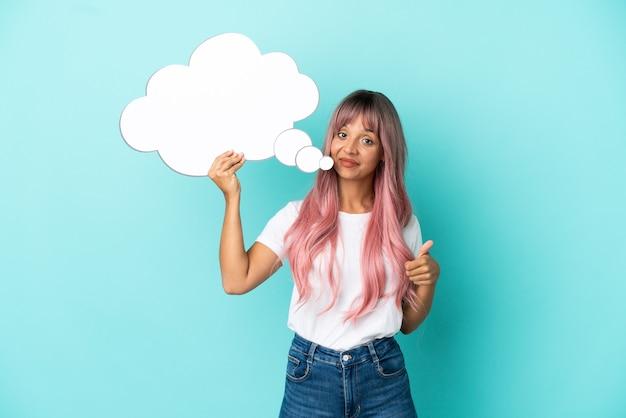 Jonge gemengd ras vrouw met roze haren geïsoleerd op blauwe achtergrond met een denkende tekstballon met duim omhoog