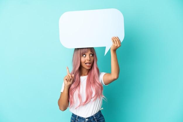 Jonge gemengd ras vrouw met roze haren geïsoleerd op blauwe achtergrond met een lege tekstballon en denken