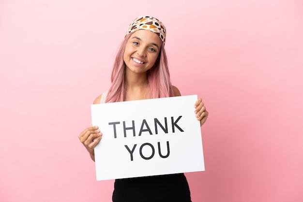 Jonge gemengd ras vrouw met roze haren geïsoleerd op roze achtergrond met een bordje met tekst dank u met gelukkige uitdrukking
