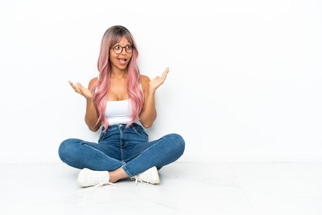 Jonge gemengd ras vrouw met roze haren zittend op de vloer geïsoleerd op een witte achtergrond met verrassing gezichtsuitdrukking