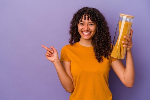 Jonge gemengd ras vrouw met spaghetti geïsoleerd op paarse achtergrond glimlachend en opzij wijzend, iets tonen op lege ruimte.