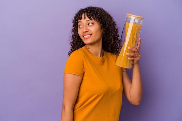 Jonge gemengd ras vrouw met spaghetti geïsoleerd op paarse achtergrond kijkt opzij glimlachend, vrolijk en aangenaam.