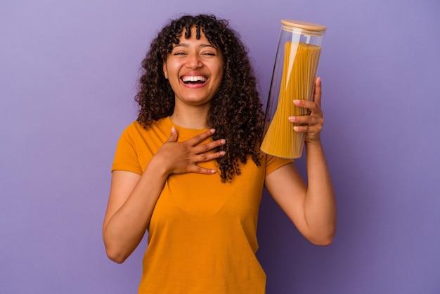 Jonge gemengd ras vrouw met spaghetti geïsoleerd op paarse achtergrond lacht hardop terwijl ze de hand op de borst houdt.