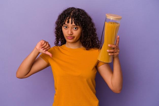 Jonge gemengd ras vrouw met spaghetti geïsoleerd op paarse achtergrond met een afkeer gebaar, duim omlaag. onenigheid begrip.