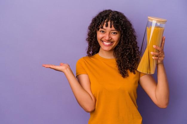 Jonge gemengd ras vrouw met spaghetti geïsoleerd op paarse achtergrond met een kopie ruimte op een palm en met een andere hand op de taille.