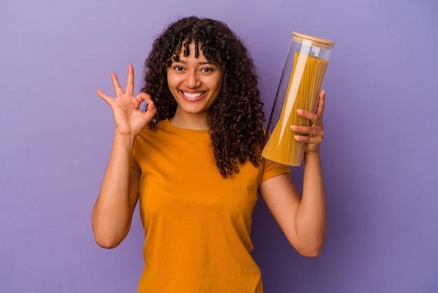 Jonge gemengd ras vrouw met spaghetti geïsoleerd op paarse achtergrond vrolijk en zelfverzekerd weergegeven: ok gebaar.
