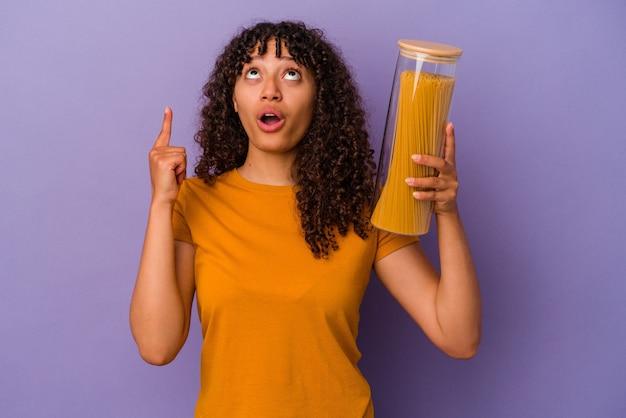 Jonge gemengd ras vrouw met spaghetti geïsoleerd op paarse achtergrond wijzend ondersteboven met geopende mond.