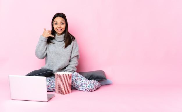 Jonge gemengd ras vrouw popcorn eten tijdens het kijken naar een film