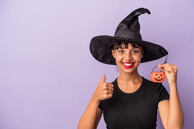 Jonge gemengd ras vrouw vermomd als een heks geïsoleerd op paarse achtergrond glimlachend en duim omhoog