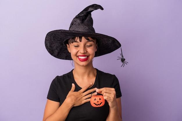 Jonge gemengd ras vrouw vermomd als een heks geïsoleerd op paarse achtergrond lacht hardop terwijl ze de hand op de borst houdt.
