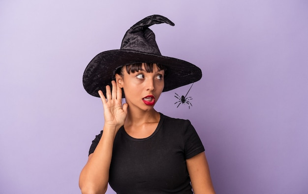 Jonge gemengd ras vrouw vermomd als een heks geïsoleerd op paarse achtergrond probeert te luisteren naar een roddel.