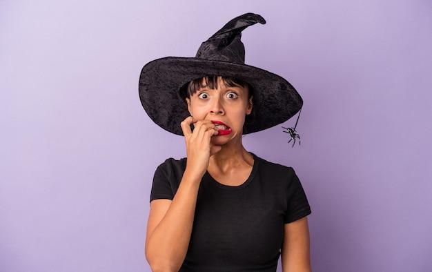 Jonge gemengd ras vrouw vermomd als een heks geïsoleerd op paarse achtergrond vingernagels bijten, nerveus en erg angstig.