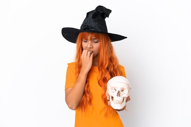 Jonge gemengd ras vrouw vermomd als heks met een schedel geïsoleerd op een witte achtergrond met twijfels