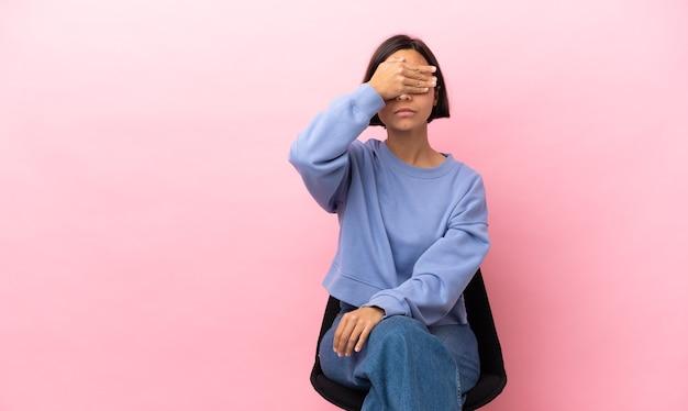 Jonge gemengd ras vrouw zit een stoel geïsoleerd die ogen bedekt door handen. wil je iets niet zien