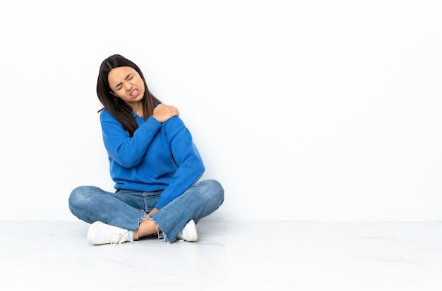Jonge gemengd ras vrouw zittend op de vloer geïsoleerd op een witte muur die lijden aan pijn in de schouder voor een inspanning