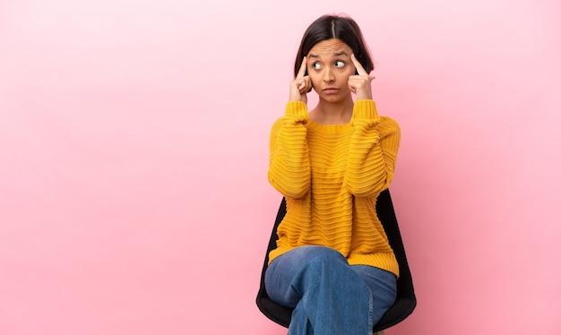 Jonge gemengd ras vrouw zittend op een stoel geïsoleerd op roze achtergrond met twijfels en denken