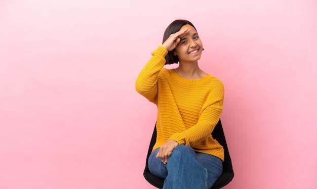Jonge gemengd ras vrouw zittend op een stoel geïsoleerd saluerend met de hand met gelukkige uitdrukking