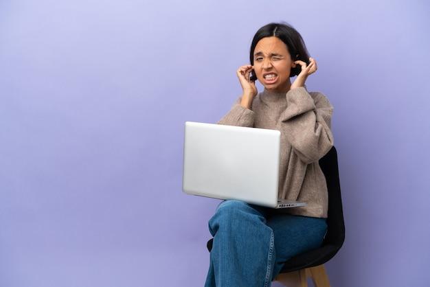 Jonge gemengd ras vrouw zittend op een stoel met laptop geïsoleerd op paarse achtergrond gefrustreerd en die oren bedekt