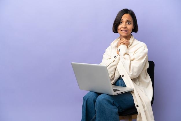 Jonge gemengd ras vrouw zittend op een stoel met laptop geïsoleerd op paarse achtergrond lachen