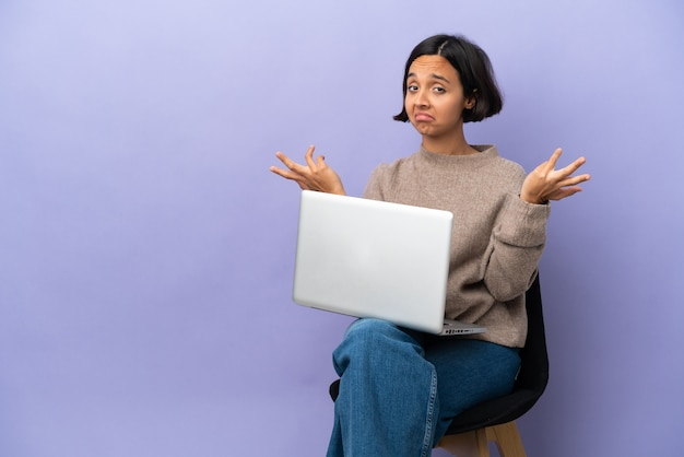 Jonge gemengd ras vrouw zittend op een stoel met laptop geïsoleerd op paarse achtergrond twijfels