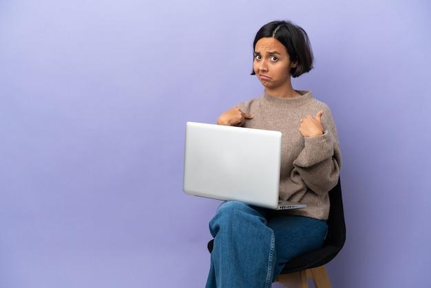Jonge gemengd ras vrouw zittend op een stoel met laptop geïsoleerd op paarse achtergrond wijzend naar zichzelf one