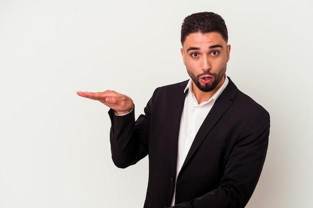 Jonge gemengd ras zakenman geïsoleerd op een witte achtergrond geschokt en verbaasd met een kopie ruimte tussen handen.