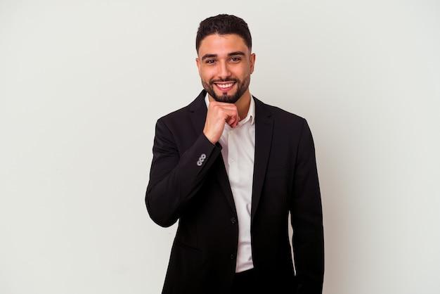 Jonge gemengd ras zakenman geïsoleerd op een witte achtergrond glimlachend gelukkig en zelfverzekerd, kin met de hand aan te raken.