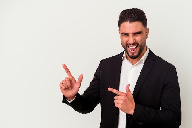 Jonge gemengd ras zakenman geïsoleerd op een witte achtergrond wijzend met wijsvingers naar een kopie ruimte, opwinding en verlangen uitdrukken.