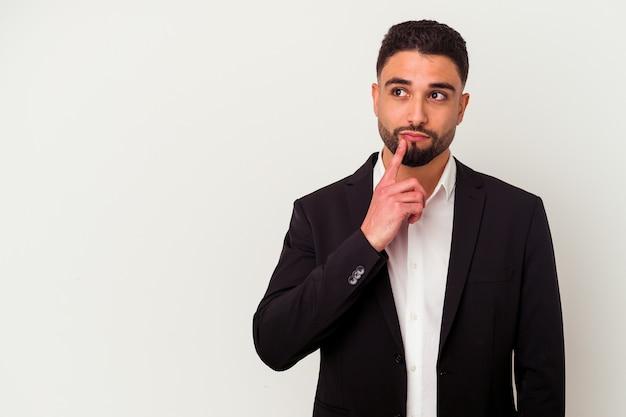 Jonge gemengd ras zakenman geïsoleerd op wit zijwaarts kijken met twijfelachtige en sceptische uitdrukking.