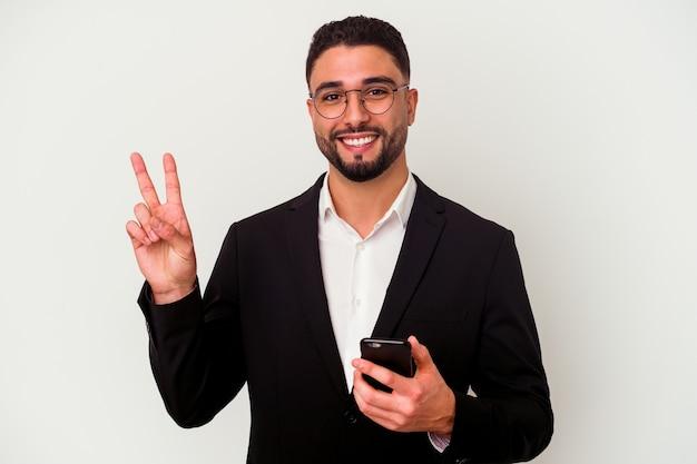 Jonge gemengd ras zakenman met een mobiele telefoon man geïsoleerd op een witte achtergrond vrolijk en zorgeloos met een vredessymbool met vingers.