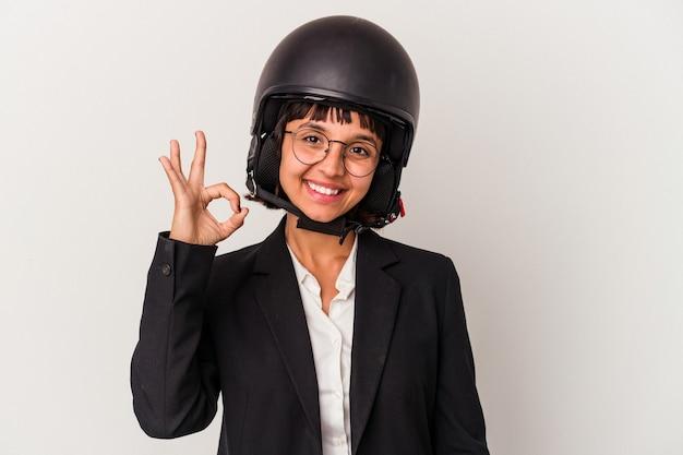 Jonge gemengd ras zakenvrouw die een motorhelm draagt, isoleerde vrolijk en zelfverzekerd met een goed gebaar.